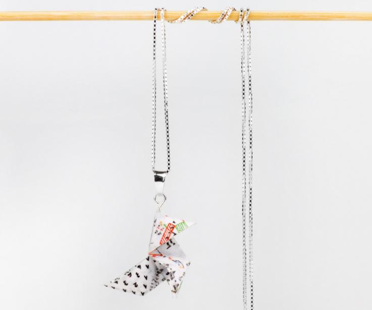 Vista frontal de un colgante con cadena de plata rematada en una hermosa pajarita de papel ilustrada con números y fórmulas matemáticas de colores.