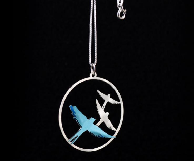 Primer plano de colgante circular tallado con siluetas de avecillas, cadena fina de plata y aplique de artesanía con forma de pájaro de papel azul.