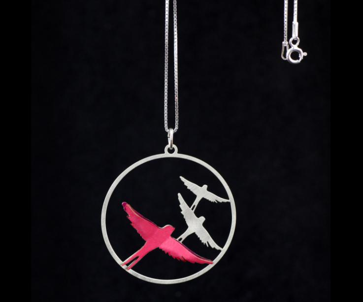 Frontal shot of silver chain with carved hoop pendant with silhouettes of flying birds and a pink paper bird mounted with 3D effect.