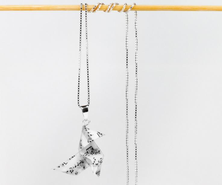 Plano frontal de colgante con cadena de plata rematada en una pajarita hecha con una partitura de papel ennoblecida con fina capa de barniz semi brillo.