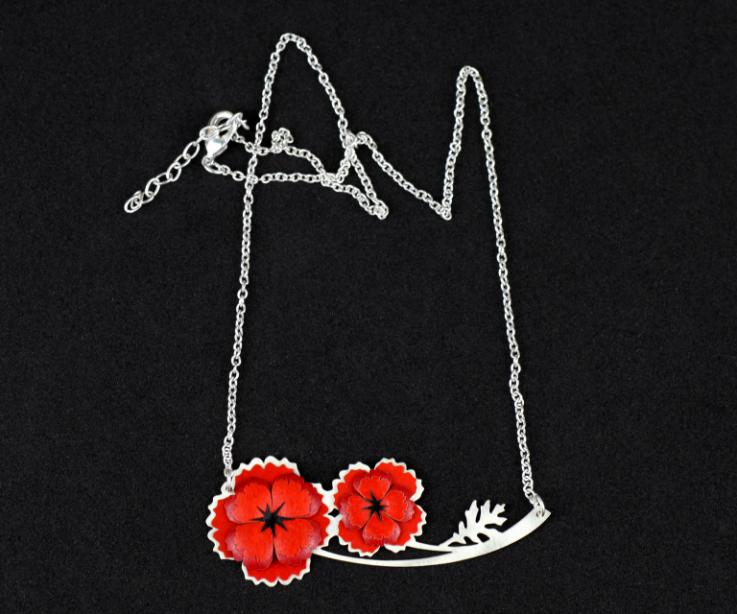 Close-up of a necklace with two red poppy flowers made of paper pieces and set to a die-cut base with branches and a thin silver chain.
