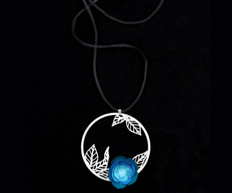 Long black cord necklace with silver tops, hoop pendant with carved leaves and a blue paper camellia flower hardened in detail view.