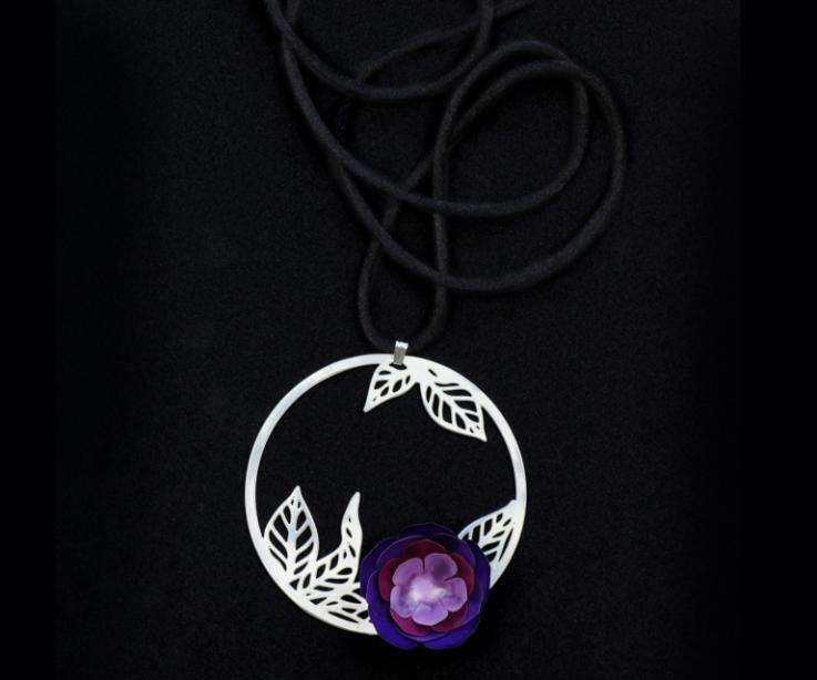 Detail view of a carved pendant with a mauve paper camellia flower, over a filigree leaves hoop and a black satin cord.