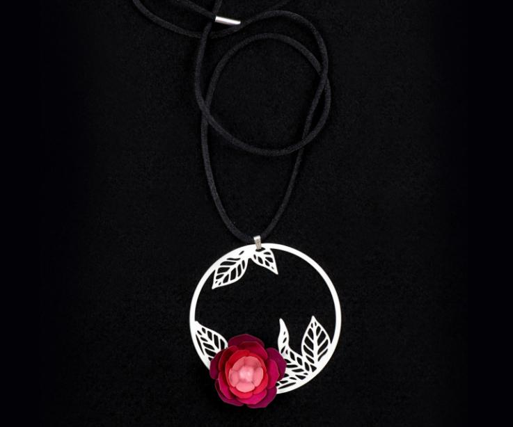 Close-up of a carved pendant with a camellia flower made of pink paper, mounted on a hoop with filigree leaves and black lace.