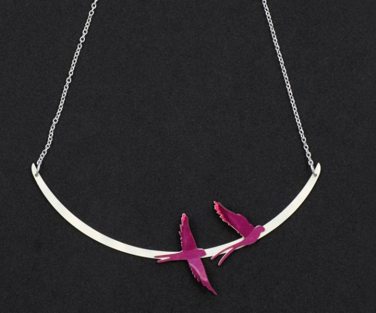 Dos pájaros de artesanía en papel de color malva con efecto 3D, montados en un semi óvalo plateado y engarzado a un collar corto de pequeños eslabones.