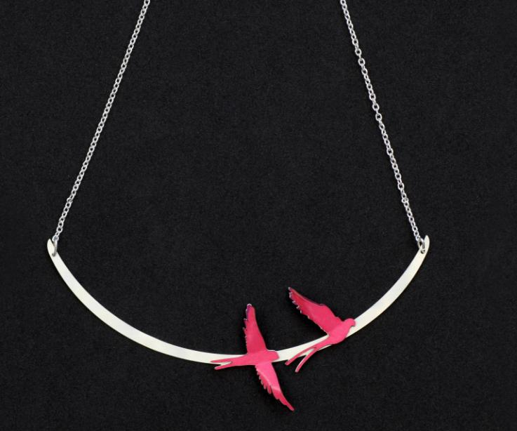 Close-up of a semi-rigid silver plated necklace, with two birds assembled with 3D effect in layers of hardened paper in pink tones.