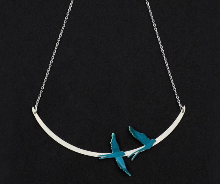 Close-up of a short silver necklace with a rigid base, chain and two paper bird settings made with layers of aquamarine tones.