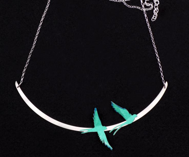 Silver necklace with two handcrafted birds in layers of blue-green paper set on a semi-oval piece with a chain of links.
