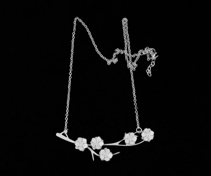 Vista frontal de cadena plateada con fornitura de rama rematada en cinco engastes de florecillas de almendro de papel blanco con un ligero acabado brillo.