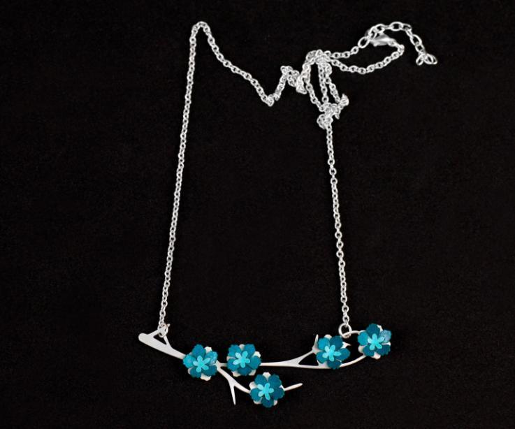 Primer plano de un colgante con cadena plateada y pequeñas flores de papel de tonos celúreos engastadas en una elegante fornitura en forma de rama.