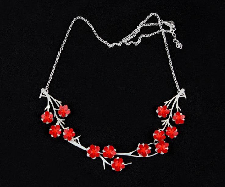 Primer plano de colgante con cadena de eslabones e incrustaciones de pequeñas flores de papel 3D en color rojo engastadas a estructura ligera de ramas.