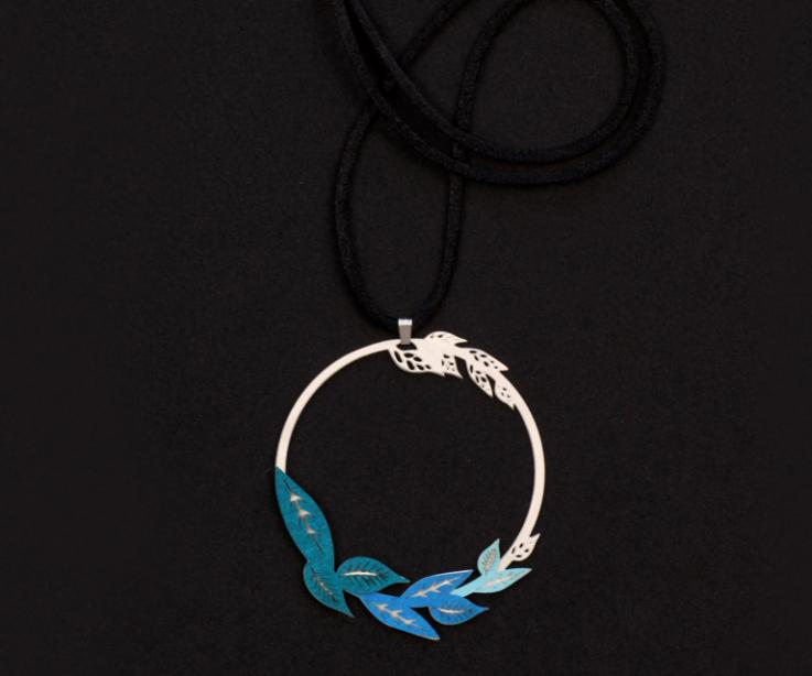 Frontal shot of circular pendant with blue paper leaves set in a filigree of carved foliage and long black cord in blurred plane.