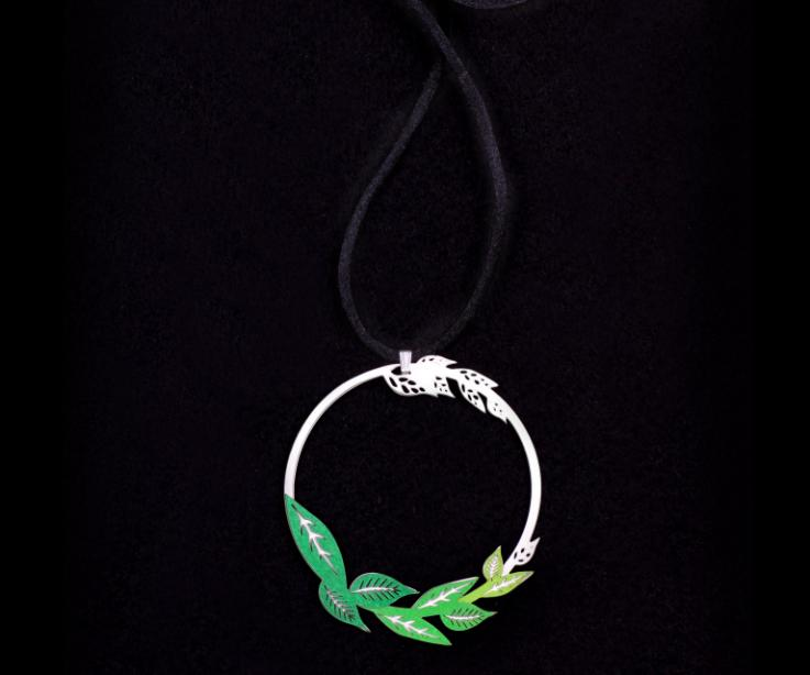 Front view of a silver circular pendant, with filigree and paper leaves in green tones set and a long black satin cord.