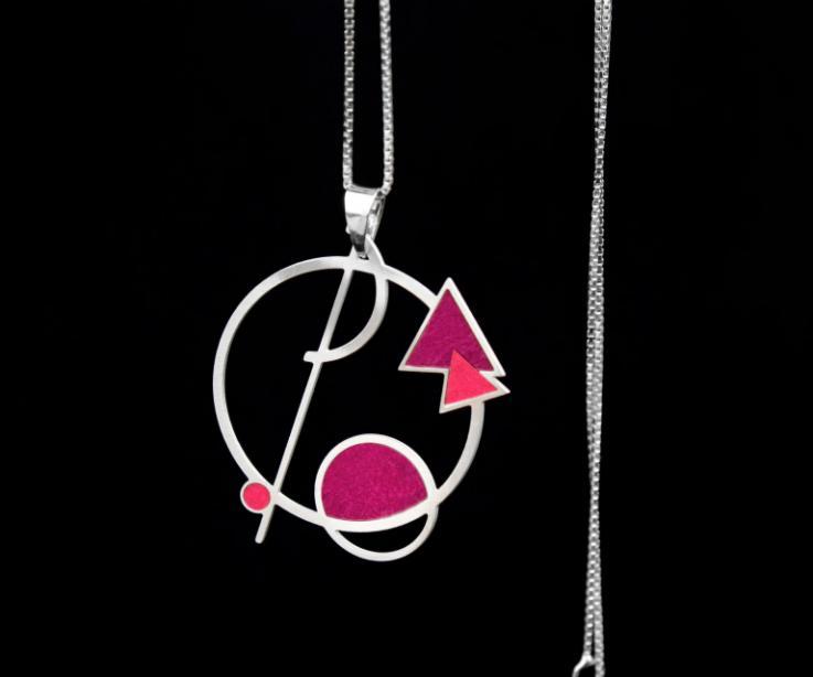 Colgante de diseño abstracto con líneas círculos y triángulos superpuestos con engastes de papel malva y vista parcial de una elegante cadena plateada.