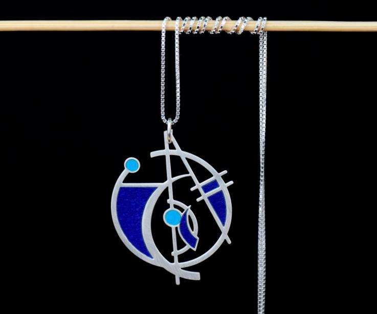 Plano frontal de un collar con dije de figuras geométricas vaciadas y superpuestas sobre las que se añaden pequeños vivos de papeles en tonos azules.