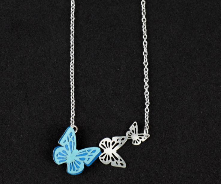 Collar plateado con tres mariposas talladas en distintos tamaños, una de ellas con engaste de alas de papel troquelado en tonalidades azules y con efecto relieve.