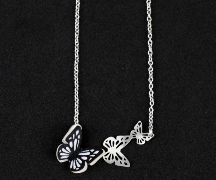 Collar con una mariposa negra de papel montada sobre una base plateada con tres alevillas volando, talladas y engarzadas a una cadena de eslabones.