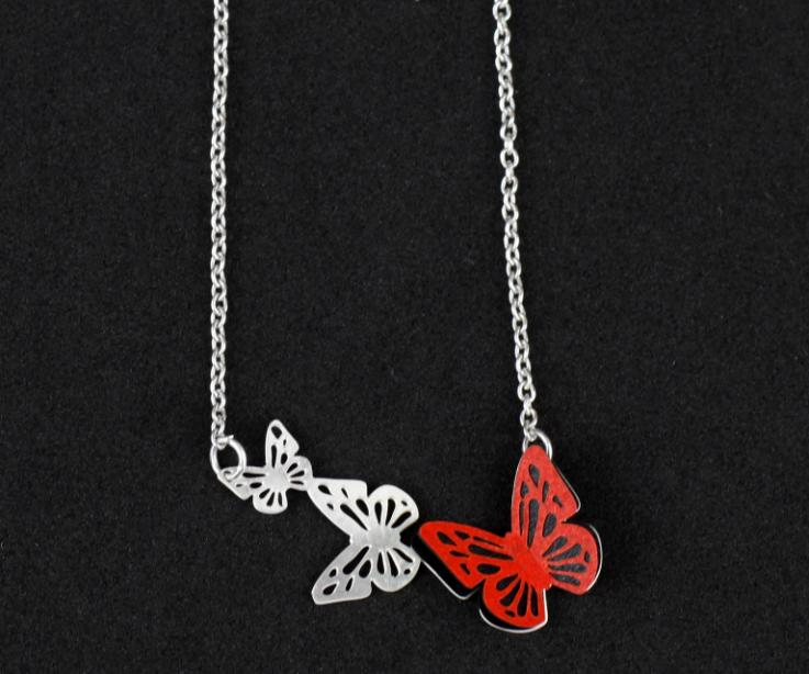 Close-up of a necklace with a butterfly made of red paper, set on a base of die-cut butterflies and attached to a silver chain.