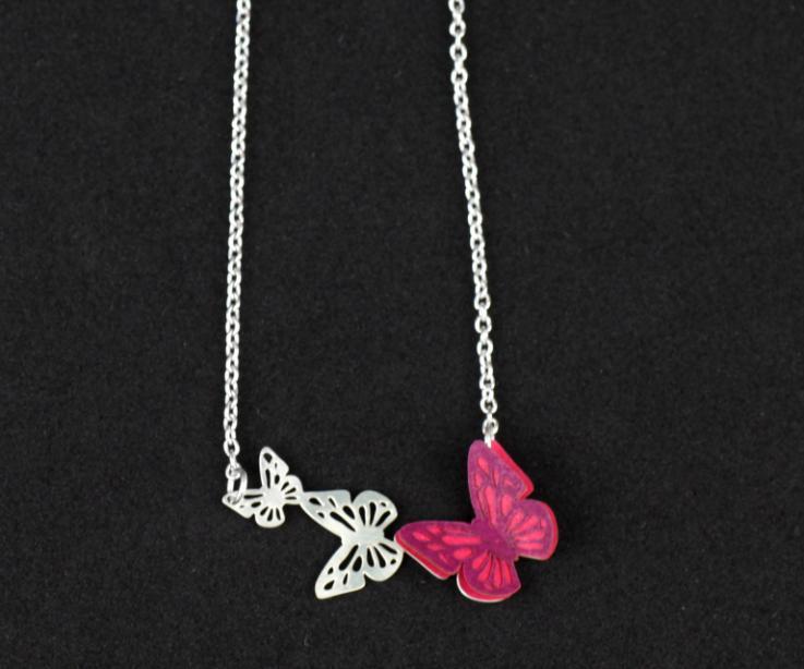 Vista frontal de collar con cadena de eslabones y tres mariposas talladas, una de las cuales tiene alas semi abiertas de papel troquelado en color rosa.