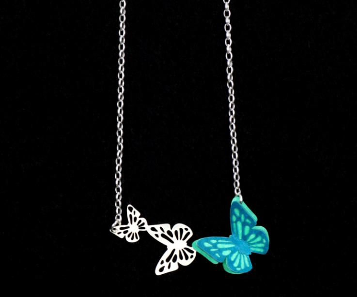 Necklace with a butterfly with 3D effect and turquoise layers of strong paper mounted on a silver base with carved butterflies and fine chain.