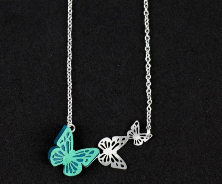 Silver necklace with a handmade paper butterfly in green tones that mounts on a pendant of butterfly silhouettes set on a chain.