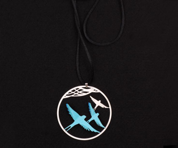 Long black lace necklace with silver pendant and carved hoop with silhouettes and two paper birds set in blue.
