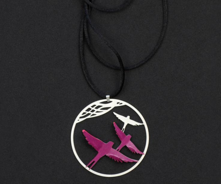 Primer plano de colgante plateado, con dos pájaros de papel de color morado engastados en un disco cincelado y sección de un cordoncillo negro.