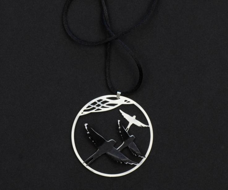 Frontal shot of a silver pendant with two birds' appliqués of black and white paper layers on a filigree hoop with black cord.