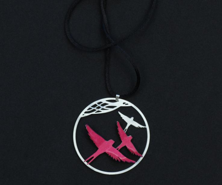Pendant with two birds of pink paper layers with a volume effect, mounted on a silver hoop and attached to a black cord in a blurred plane.