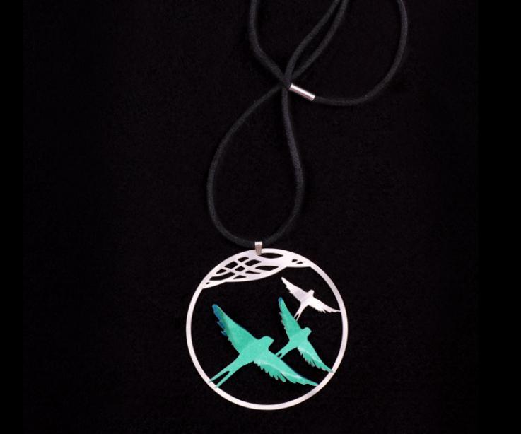 Vista frontal de un dije circular con filigrana plateada, dos pájaros de papel color verde engastados, y un cordoncillo negro de raso con aplique de plata.