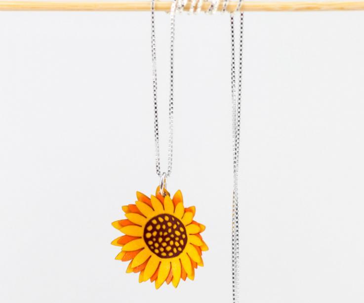 Primer plano de colgante en forma de flor de girasol amarillo de capas de papel con efecto tridimensional que se engarza a una cadena de estilo veneciano.