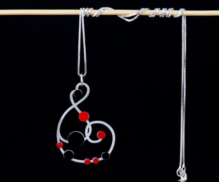 Vista frontal de un collar largo plateado con cadena fina y un hermoso dije de formas sinuosas embellecido con pequeños círculos de papel rubí y negro.