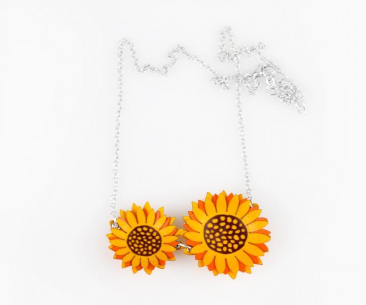 Primer plano de un collar con dos flores amarillas de girasol modeladas con varias capas de papel y efecto relieve, engastadas a una cadena plateada.