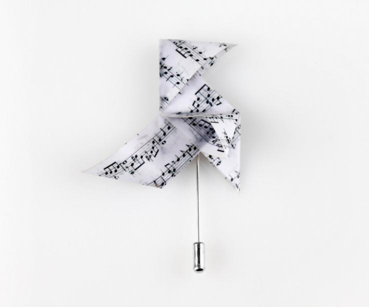 Close-up of an elegant and original silver needlepoint pin topped with a 3D paper origami bird with musical illustration, on a white background.