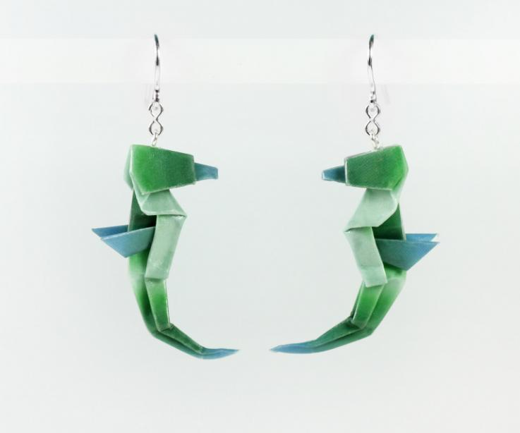 Silver and paper earrings shaped like a green seahorse