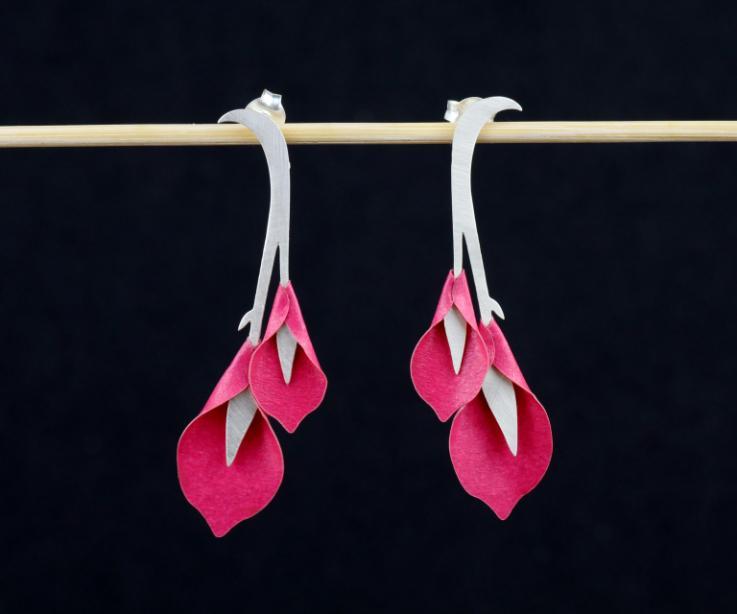 Plano frontal de un par de arracadas con base de ramitas labradas y dos flores de calas en papel semi brillo de tonos rosas con cierres ocultos en plata.