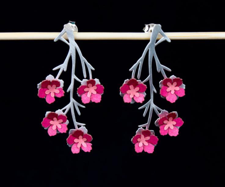 Plano frontal de zarcillos con original diseño invertido de ramas de metal y engastes de flores de almendro 3D elaboradas con papel rosa semi brillo.