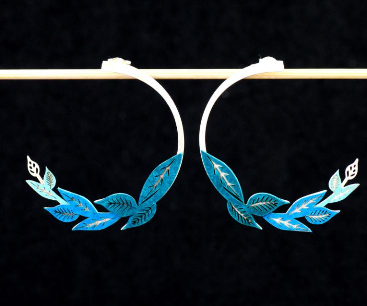 Front view of two earrings with sterling silver clasps and carved sections inlaid with blue-toned die-cut paper.