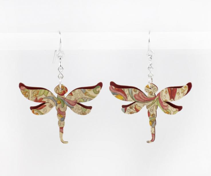Fashionable dragonfly earrings on paper, front view