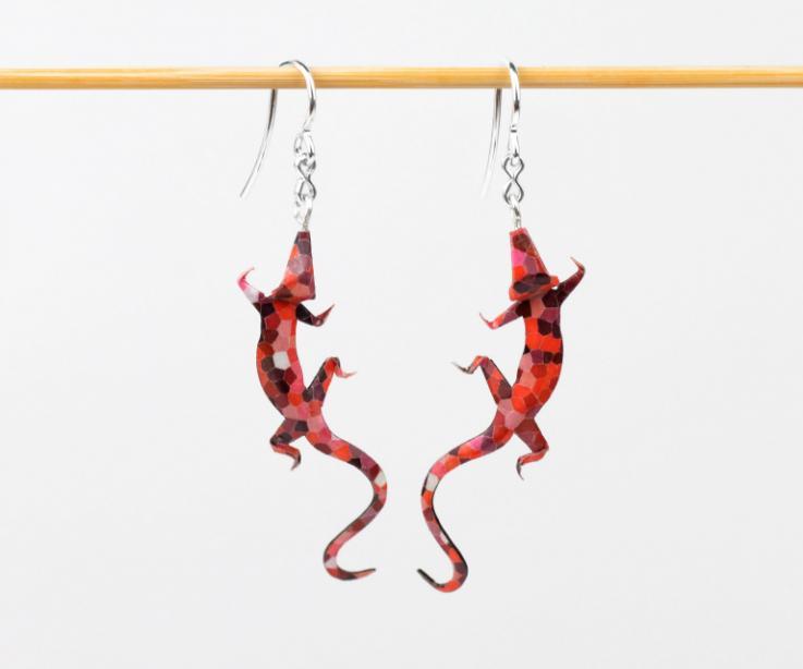Vista frontal de un par de pendientes con forma de salamandra de fina artesanía realizados en origami y plata de ley.