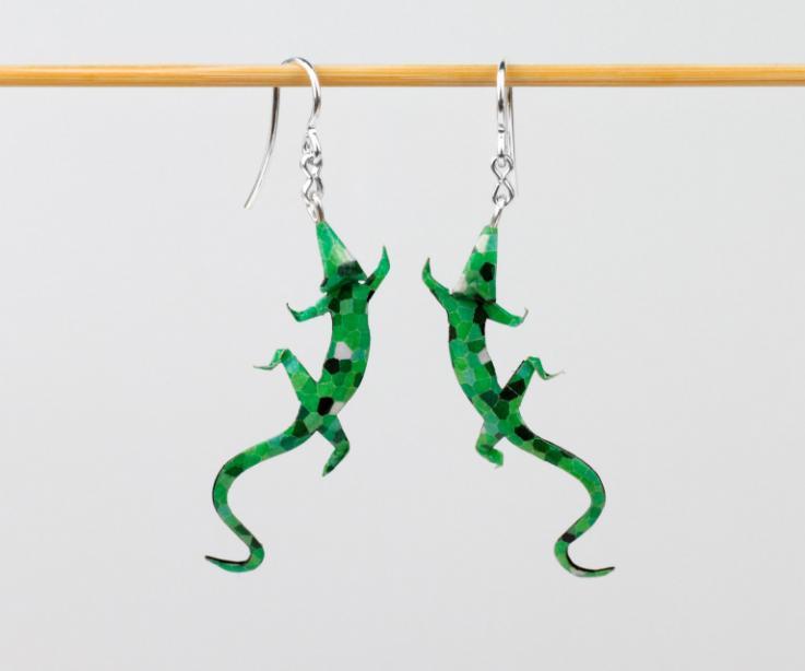 Vista frontal de unos elegantes pendientes lagartija en tonos verdes, unos pendientes que corretearan por todos tus looks a un precio low-cost.