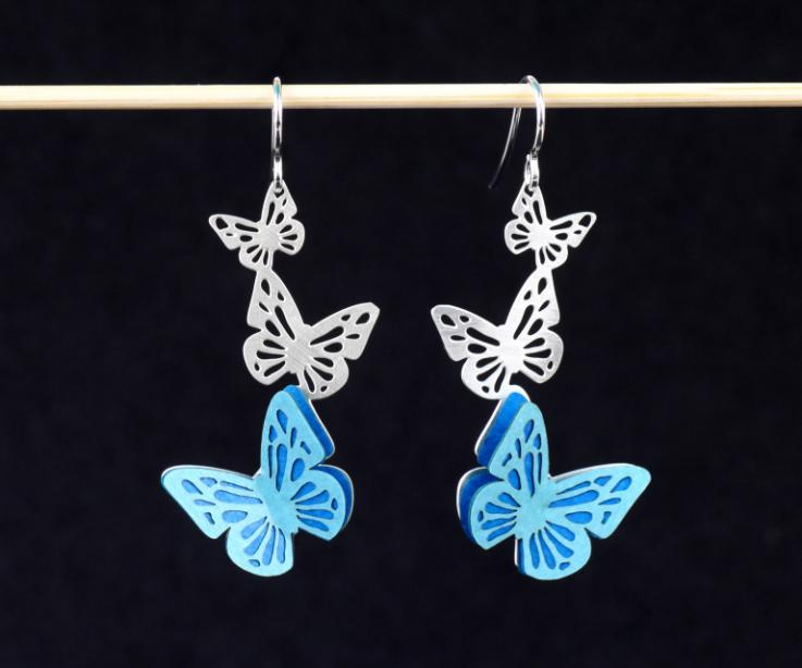 A pair of silver earrings, with butterflies carved at the base, set with small blue paper wings, and fine silver clasps.