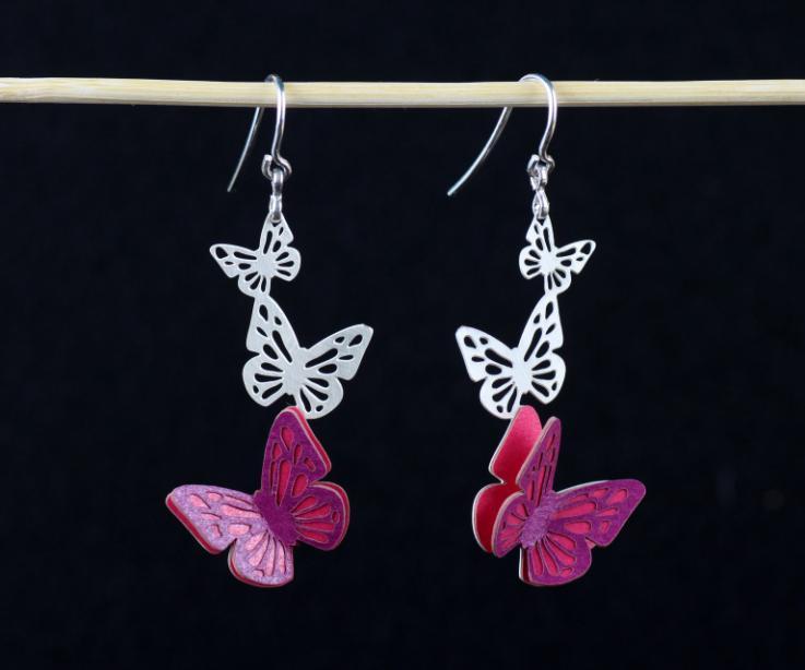 Vista frontal de dos zarcillos con cierre de gancho en plata y tres mariposas talladas en una única pieza, con alas de papel endurecido de color malva.