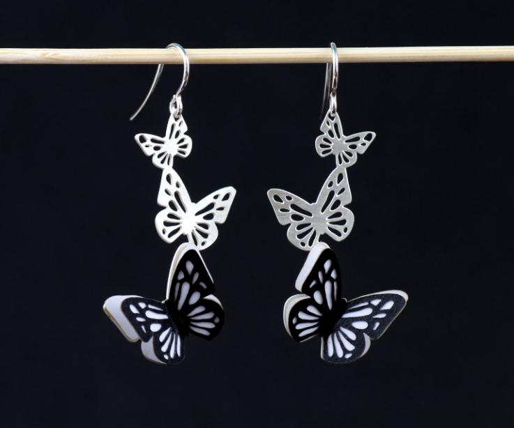 Two earrings with silver hooks, carved butterflies and a pair of wings made of hardened paper, stamped and set in black and white.