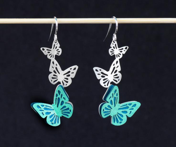 Two long earrings with silver hooks and three carved butterflies, one of which is set with wings of die-cut and hardened paper, in green tones.
