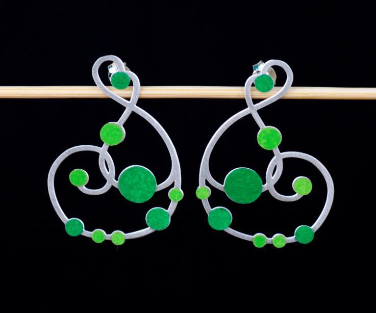 Vista frontal de un par de pendientes plateados con cierre de tuerca y diseño sinuoso recorrido con incrustaciones de círculos de papel en tonos verdes.