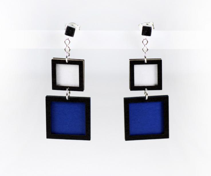 Mondrian earrings consisting of two squares on white paper and blue, front view
