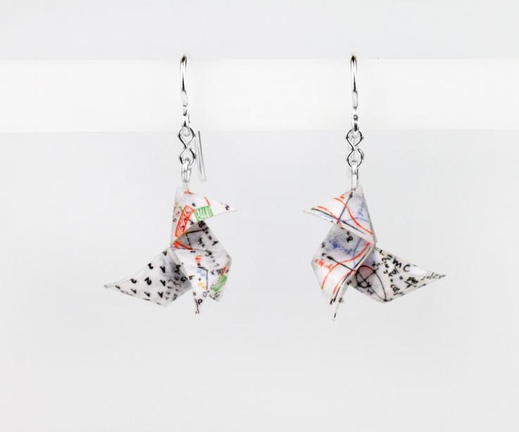 Shot of earrings with silver hooks and printed paper origami birds with numbers and mathematical calculations of colors and varnish with a semi-gloss finish.