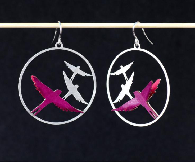 Vista frontal de dos aretes con cierre de gancho en plata y filigrana de pájaros volando sobre los que se montan avecillas en capas de papel de color lila.