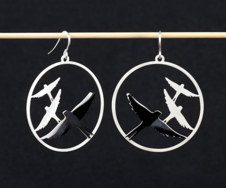 Two silver earrings with silver hook clasp, filigree of flying birds and overlapping layers of black and white paper with volume effect.